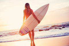 Surfer girl on the beach at sunset Stock Photos