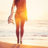 Surfer girl on the beach at sunset Royalty Free Stock Photography