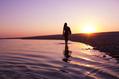 Surfer Girl. Beautiful surfer girl walking in the beach with her surfboard at sunset Stock Photography