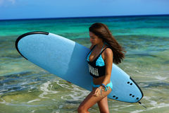 Surfer girl with board at beach Stock Photography