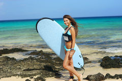 Surfer girl with board at beach Royalty Free Stock Image
