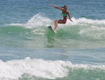 Surfer Girl Carving a Wave in the Outer Banks of NC royalty free stock image