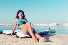 Surfer girl close to water on city beach royalty free stock images