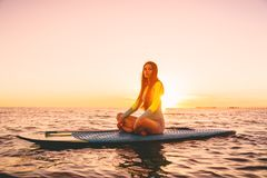 Surfer girl on stand up paddle board, quiet sea with warm sunset colors. royalty free stock images