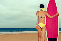 Surfer girl standing on the beach withsurf board Royalty Free Stock Photos