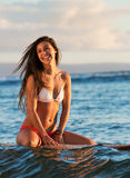Surfer girl at sunset in Hawaii Stock Photo