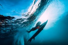 Surfer girl with surfboard dive underwater with fun under big ocean wave. royalty free stock photo