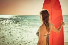 Surfer girl with surfboard near the ocean Stock Photography