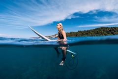 Surfer girl with surfboard relaxing at line up in ocean stock image