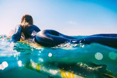 Surfer woman on the surfboard. Woman with surfboard in ocean during surfing Stock Photo