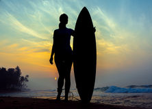 Surfer girl surfing looking at ocean beach sunset. Silhouette  w Stock Images