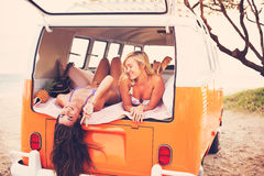 Surfer Girls Beach Lifestyle. Beautiful Surfer Girls Relaxing in the Back of Classic Vintage Surf Van on the Beach at Sunset Stock Photo