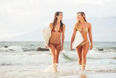Surfer Girls on the Beach at Sunset in Hawaii Stock Photography