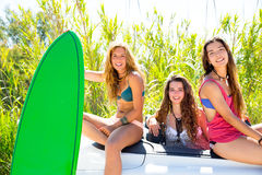 Surfer girls group holding happy surfboards on convertible car Stock Photos