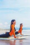 Surfer girls stretching near the ocean Stock Photos