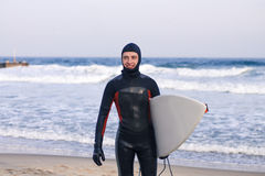 Surfer goes out of water wearing a wetsuit Stock Photo