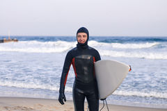 Surfer goes out of water wearing a wetsuit Royalty Free Stock Photos