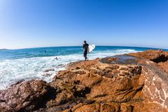Surfer Going Surfing Ocean Rocks. Surfer going surfing on winter blue day with entry into ocean water off rocky coastline royalty free stock images