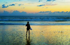 Surfer going to surf ocean. Surfer going to surf in the ocean at sunset. Bali island, Indonesia Royalty Free Stock Photo