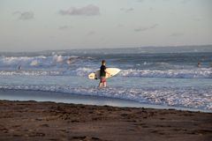 Surfer at Cannggu Echo Beach in Bali Indonesia stock photo