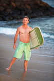 Surfer in Green Shorts with Surfboard. Happy male surfer standing on Maui waterfront Stock Image