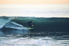 Surfer on Green Surfboard Inside Water Wave Royalty Free Stock Images