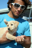 Surfer guy and his dog. Young man holding his labrador puppy Royalty Free Stock Photography