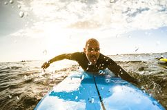 Surfer guy paddling with surfboard at sunset in Tenerife. With unrecognizable people at surf boards on background - Sport travel concept stock photography