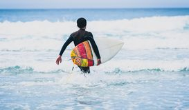 Surfer guy with surfboard in hand running towards big waves. Man in surfing wet suit is running in the waves of cold atlantic ocean in Galicia, Spain royalty free stock photography