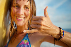 Surfer. Happy smiling lady surfer showing shaka sigh. Focus on the hand Royalty Free Stock Images