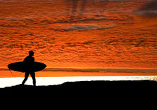 Surfer heading for ocean as the sun sets Royalty Free Stock Photos