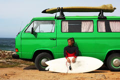 Surfer with his retro van. Surfer preparing to go surfing with his green vintage van Royalty Free Stock Photos