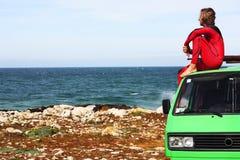 Surfer with his retro van. Surfer watching the ocean on top of  his green vintage van Stock Photo