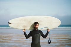 Surfer with his surfboard against the sea Royalty Free Stock Image