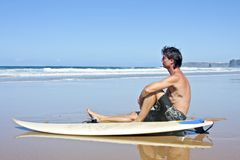 Surfer with his surfboard at the beach Royalty Free Stock Photos