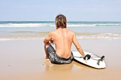 Surfer and his surfboard at the beach Royalty Free Stock Photos
