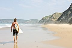 Surfer and his surfboard at the beach. Surfer and his surfboard walking along the beach ready to surf Stock Photos