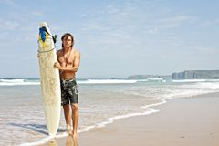Surfer and his surfboard at the beach Royalty Free Stock Photo