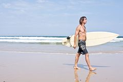 Surfer and his surfboard at the beach Royalty Free Stock Photography