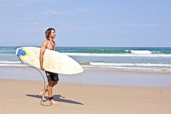 Surfer with his surfboard at the beach Royalty Free Stock Images