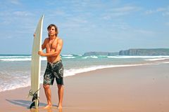 Surfer with his surfboard at the beach Stock Photos
