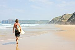 Surfer with his surfboard walking along the beach Royalty Free Stock Photos