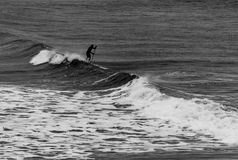 Surfer holding oar in wetsuit negotiating waves  on Tynemouth Be. Ach in UK  on a winter morning in black and white Stock Photos