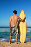Surfer holding a surf board. On beach Stock Photo