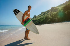 Surfer holding a surf board on beach. Full length shot of young man with surf board on beach. Male surfer holding surfboard on the sea shore and looking away Royalty Free Stock Images
