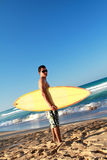 Surfer holding a surfboard on beach. Surfer holding a surfboard on tropical beach Royalty Free Stock Photo