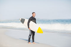 Surfer holding a surfboard on the beach. On the sunny day Royalty Free Stock Image