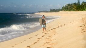 Surfer holding surfboard and walking on the beach Hawaii