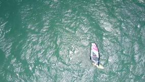 Surfer holds sail swimming in turquoise ocean