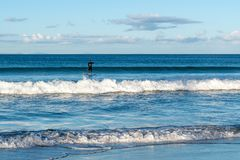 Surfer idling on the shallow sea waves. Single surfer idling on the shallow waves of a blue sea royalty free stock photos